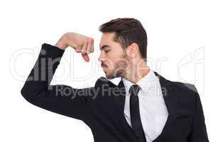 Cheerful businessman tensing arm muscle