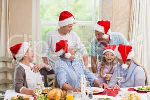 Happy extended family in santa hat speaking together