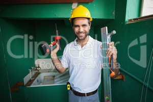 Construction worker holding spirit level and drill