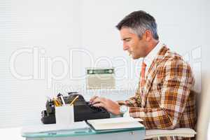 Retro man with cigarette typing on typewriter