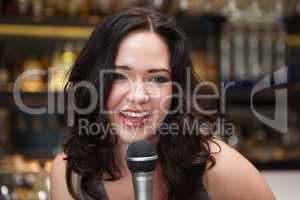 Happy brunette singing into mic