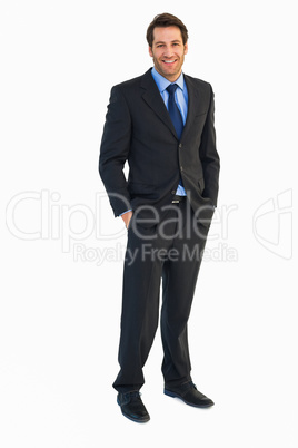 Smiling young businessman with hands in pockets