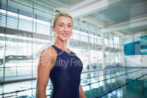 Smiling female swimmer by pool at leisure center