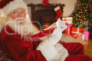 Smiling santa writing list with a quill