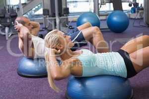 Fit couple doing abdominal crunches at gym