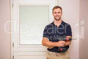 Construction worker holding power tool with arms crossed