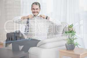 Happy businessman sitting on his couch seen through glass