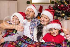 Happy family in santa hat hugging under the cover
