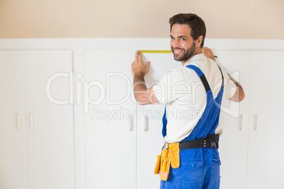 Handyman measuring a wardrobe