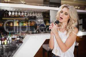 Pretty blonde woman singing while closing her eyes