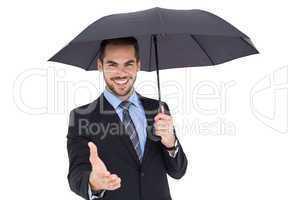 Happy businessman under umbrella offering handshake