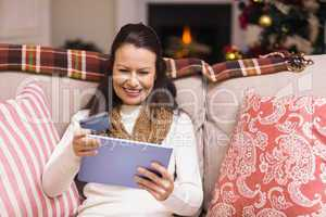 Festive brunette woman using her credit card and tablet pc
