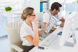 Blonde editor looking over contact sheet at her desk