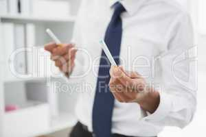 Mid section of a businessman holding cigarettes