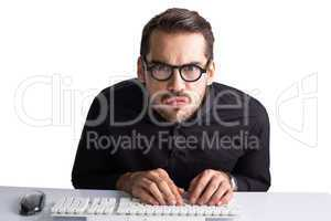 Concentrated businessman with glasses typing on keyboard