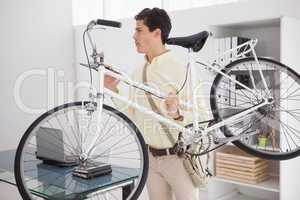 Casual businessman carrying his bicycle