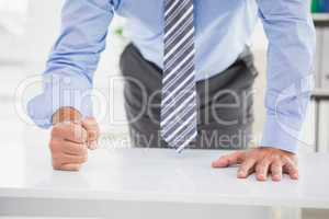 Businessmans fist clenched over desk