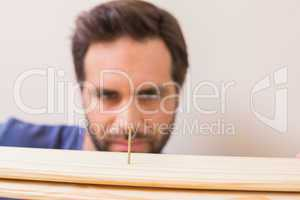 Casual man looking at nail in plank