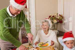 Grandfather in santa hat serving roast turkey at christmas