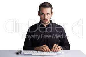 Serious businessman typing on keyboard