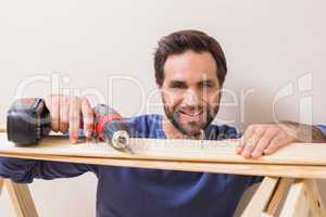 Casual man drilling nail in plank