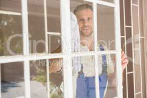 Handyman cleaning the window and smiling