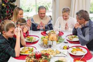 Extended family saying grace before christmas dinner
