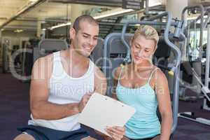 Woman discussing her performance on clipboard with a trainer at