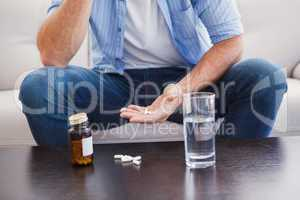 Man taking his pills on couch