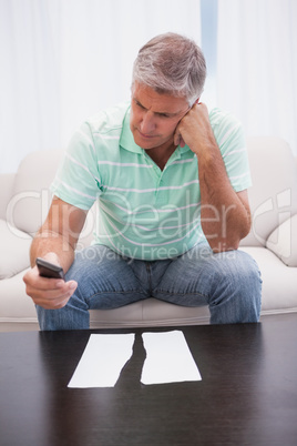 Worried man looking at ripped page sending a text