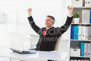 Cheering businessman at his desk