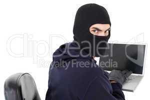 Hacker sitting and hacking laptop