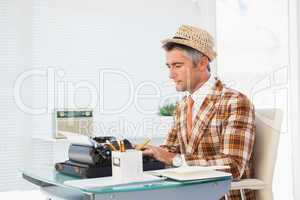 Retro man in straw hat typing on typewriter
