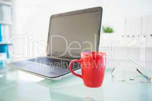 Laptop on desk with red mug and glasses