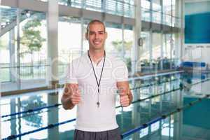 Swimming coach gesturing thumbs up by pool at leisure center