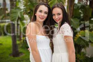 Pretty friends smiling at camera in white dresses