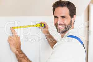 Handyman measuring a wardrobe