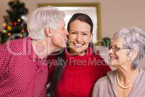 Grandfather kissing the mother at christmas