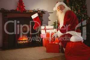 Cheerful santa delivering gifts at christmas eve