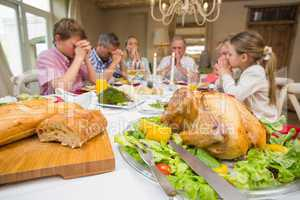 Family saying grace before christmas dinner together