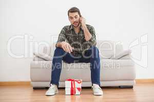 Confused man looking at gifts on floor