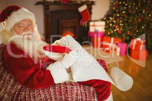 Smiling santa claus writing his list on scroll