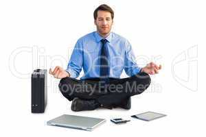 Man sitting in lotus pose with laptop, tablet and suitcase