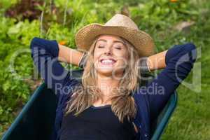 Pretty blonde lying in wheelbarrow
