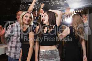Stylish friends dancing and smiling