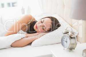Pretty brunette lying in bed sleeping