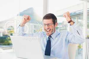 Cheering businessman at his desk