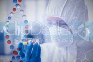 Composite image of scientist in protective suit analyzing pills