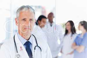 Composite image of mature doctor looking straight ahead