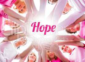 Diverse women smiling in circle wearing pink for breast cancer